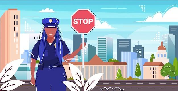 Straßenverkehrspolizei-inspektor hält stoppschild polizistin offizier in einheitlicher sicherheitsbehörde justiz rechtsdienst konzept flaches porträt stadtbild