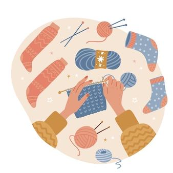 Strickprozess draufsicht auf zwei weibliche hände, die nadeln garn und fadenknäuel winterurlaub halten...