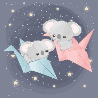 Süße kleine koalas auf einem papiervogel