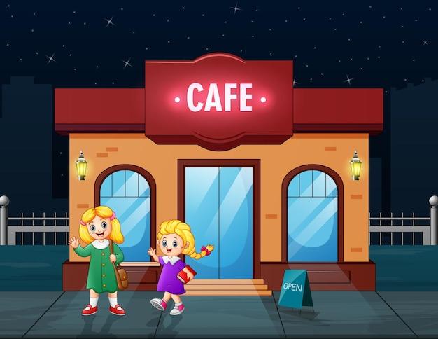 Süße zwei mädchen vor dem café