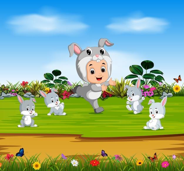 Süsser junge, der kostümkaninchen trägt und mit kaninchen spielt