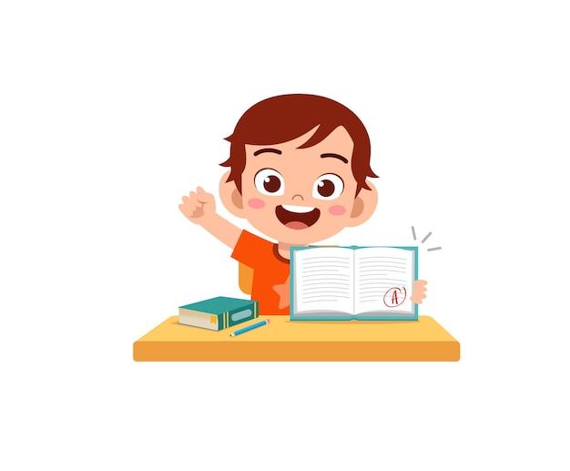 Süßer kleiner junge fühlt sich glücklich, weil er eine gute note von der prüfung bekommt