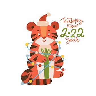 Süßer tiger in einem weihnachtsmann-kostüm mit geschenkbox sitzend in einer girlande verstrickt neujahrs- und weihnachtsgr...