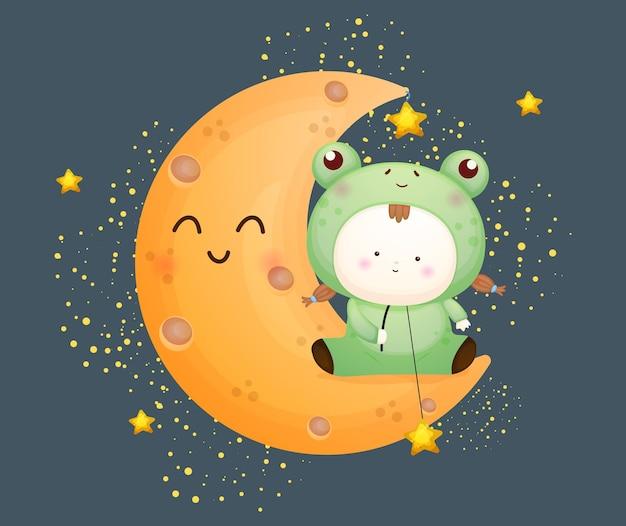 Süßes baby im froschkostüm sitzt auf dem mond. maskottchen-karikaturillustration premium-vektor
