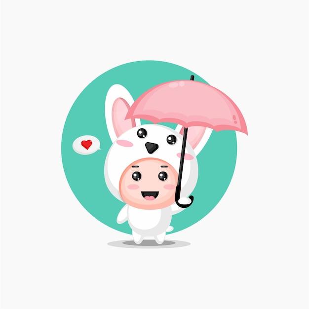 Süßes kaninchen, das einen regenschirm trägt
