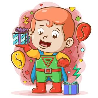 Super baby feiern seinen geburtstag mit dem super kostüm und halten das geschenk