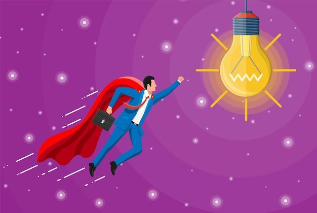 Supergeschäftsmann im roten umhang, der zur glühlampe der idee fliegt. konzept der kreativen idee oder inspiration, unternehmensgründung. glasbirne mit spirale im flachen stil. vektor-illustration