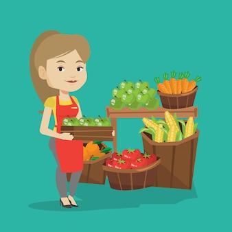 Supermarktarbeiter mit kiste voller äpfel.