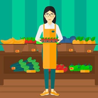 Supermarktarbeitskraft mit dem kasten voll von den äpfeln