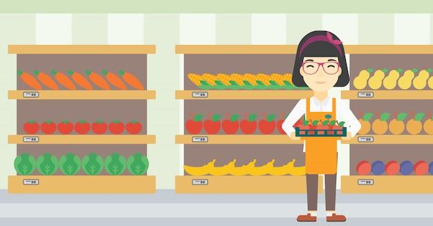 Supermarktarbeitskraft mit dem kasten voll von den äpfeln.