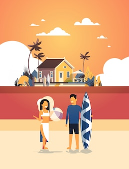 Surferpaar sommerferien mann frau surfbrett auf sonnenuntergang strand villa haus tropische insel vertikal