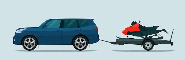 Suv-auto schleppt einen anhänger mit einem schneemobil.
