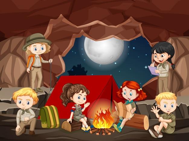 Szene mit einer gruppe von pfadfindern, die die höhle erkunden