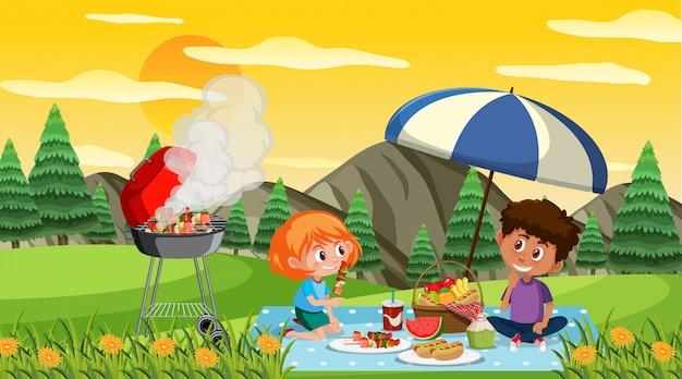 Szene mit glücklichen kindern, die im park bei sonnenuntergang essen