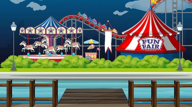 Szene mit zirkusfahrten am see bei nacht
