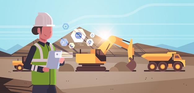 Tagebau-arbeiterin im helm mit mobilem app-bagger