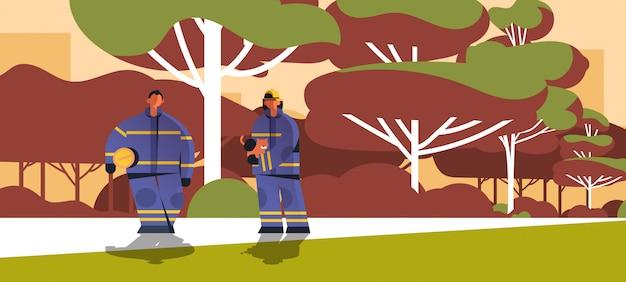 Tapfere feuerwehrmänner, die katzenfeuerwehrpaar retten, das uniform- und helmfeuerwehrnotdienst trägt, der feuerkonzeptlandschaft löscht