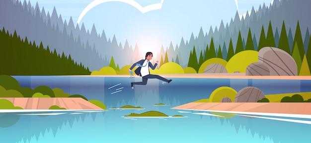 Tapferer businesman, der über fluss mit krokodilrisiko- und gefahrenoptimismus-bestimmungskonzeptgeschäftsmann springt, der zum ziel sonnenuntergang landschaftshintergrund voller länge flache horizontale läuft