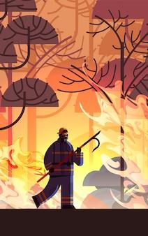 Tapferer feuerwehrmann, der den schrott löscht den gefährlichen verheerenden feuerwehrmann kämpft mit buschfeuer, das naturkatastrophenkonzept feuert intensive orange flammen in voller länge vertikale