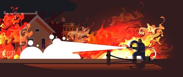 Tapferer feuerwehrmann, der flamme im brennenden hausfeuerwehrmann löscht, der uniform und helm trägt, der wasser sprüht, um feuerwehrnotfallkonzept zu feuern