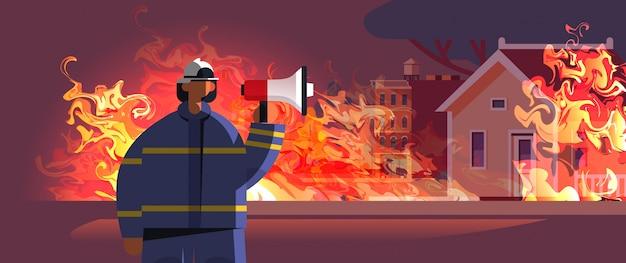 Tapferer feuerwehrmann, der lautsprecherfeuerwehrmann in uniform und helm-feuerwehr-notdienst hält, der feuerkonzept löscht, das hausaußenorangenflammenporträt brennt