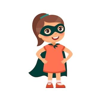 Tapferes kleines mädchen in einer heldenhaften pose und einem superheldenkostüm