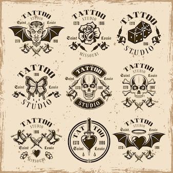 Tattoo-studio-set von neun vektoremblemen, etiketten, abzeichen oder t-shirt-drucken im vintage-stil auf schmutzigem hintergrund mit flecken und grunge-texturen