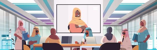 Team von arabischen medizinischen spezialisten, die videokonferenz mit weiblichem schwarzen muslimischen arzt medizingesundheitskonzept krankenhausbesprechungsrauminnenraum horizontale porträtvektorillustration haben