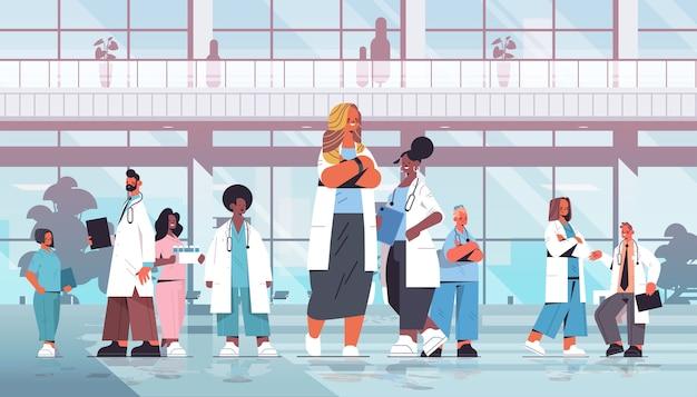 Team von mischrassenärzten in uniform, die zusammen vor der horizontalen vektorillustration des krankenhausgebäudemedizin-gesundheitskonzepts stehen