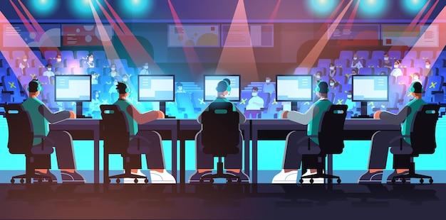 Team von professionellen virtuellen spielern, die online-videospiele auf e-sport-arena-wettbewerbsturnier-konzeptmännern in kopfhörern spielen, die vor monitoren in voller länge horizontale vektorillustration sitzen