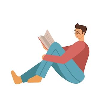 Teenager-mann in freizeitkleidung und brille am boden sitzend und buch lesen