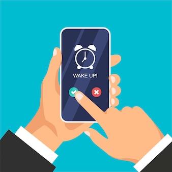 Telefon mit app-wecker auf dem bildschirm. hand hält smartphone lokalisiert auf blauem hintergrund.