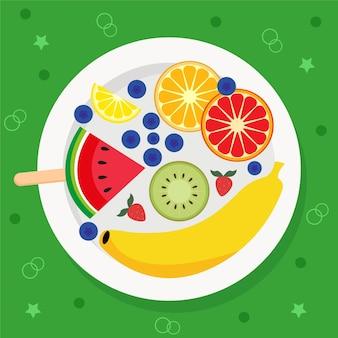 Teller mit früchten und beeren auf grünem hintergrund
