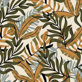 Tendenzieren sie abstraktes nahtloses muster mit bunten tropischen blättern und anlagen auf pastellhintergrund
