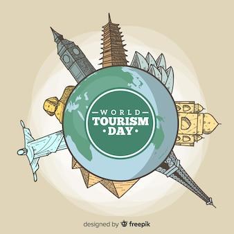 Tourismus-tageshintergrund mit welt und gezeichneten art der monumente in der hand
