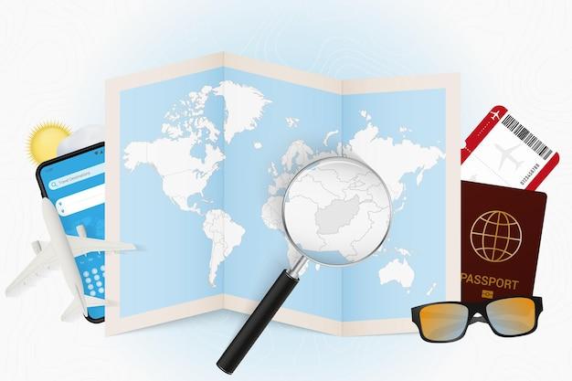 Tourismusmodell des reiseziels afghanistan mit reiseausrüstung und weltkarte