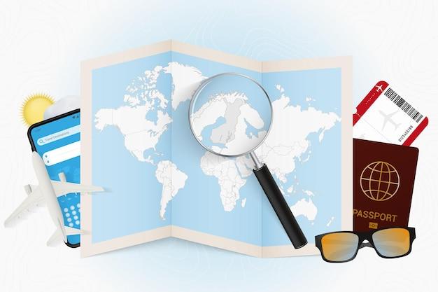 Tourismusmodell des reiseziels finnland mit reiseausrüstung und weltkarte