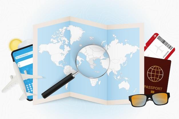 Tourismusmodell des reiseziels griechenland mit reiseausrüstung und weltkarte mit lupe