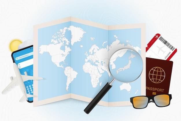 Tourismusmodell des reiseziels japan mit reiseausrüstung und weltkarte