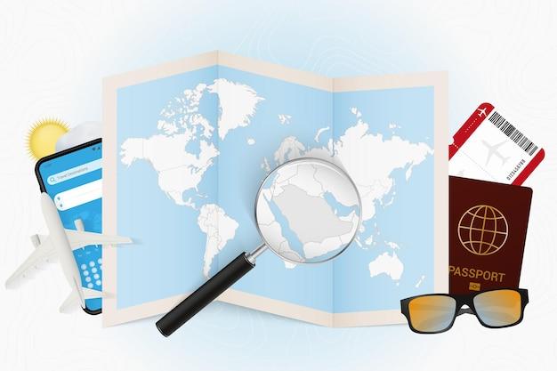 Tourismusmodell des reiseziels saudi-arabien mit reiseausrüstung und weltkarte