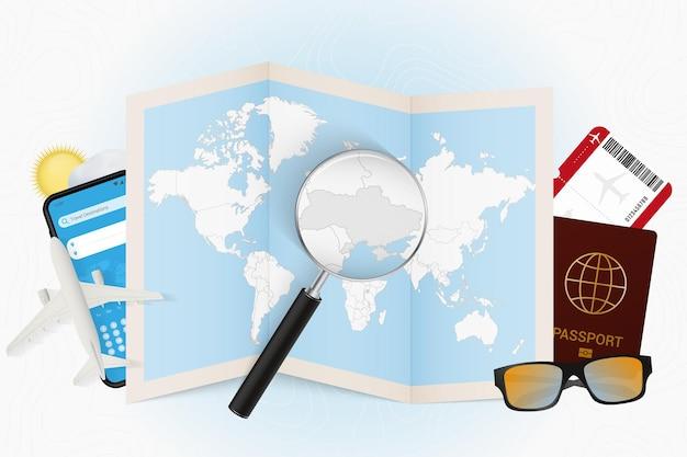 Tourismusmodell des reiseziels ukraine mit reiseausrüstung und weltkarte