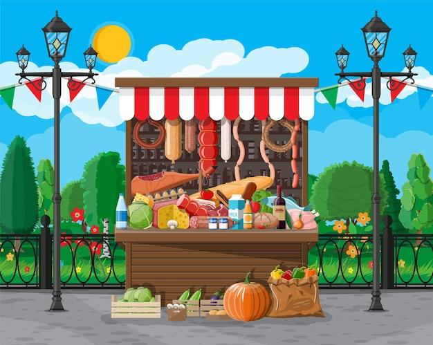 Traditioneller markt holzlebensmittelstand voller lebensmittel mit fahnen, kisten. stadtpark, straßenlaterne und bäume. himmel mit wolken und sonne. messe, lebensmittelgeschäft und shopping.