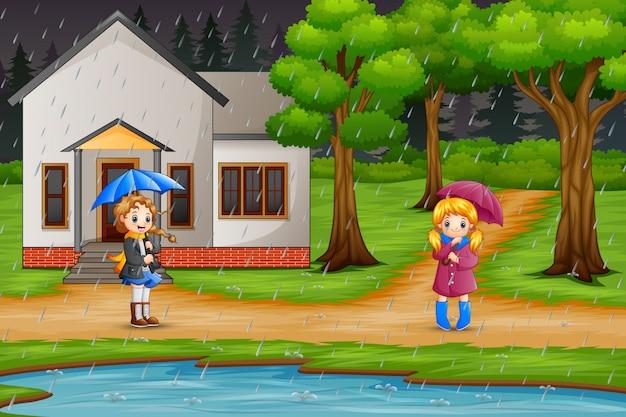 Tragender regenschirm des mädchens zwei unter dem regen
