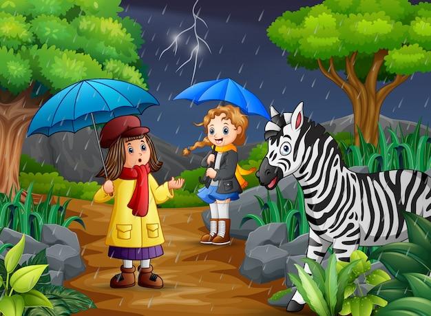 Tragender regenschirm mit zwei mädchen geht unter einen regen mit zebra