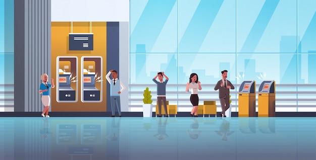 Traurige leute nahe atm-maschine ohne geldfehlerbenachrichtigungsfinanzkrisentransaktion verweigerten verschlossenen bankkreditkarteschlechtes servise am horizontalen konzept der bank in voller länge