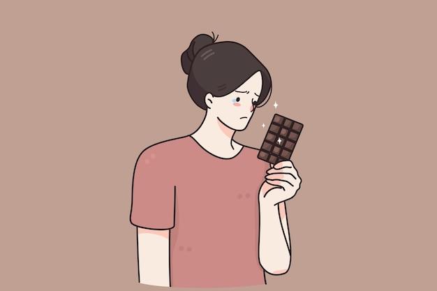 Traurige unglückliche junge frauenkarikaturfigur, die mit schokolade in der hand steht