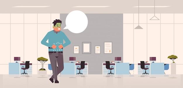 Trauriger geschäftsmannmann mit blassem gesicht erbrechen übelkeit magenschmerzen essen oder alkoholvergiftung verdauungsproblem konzept kerl mit chat-blase, die krankes modernes büroinnenraum in voller länge horizontal fühlt