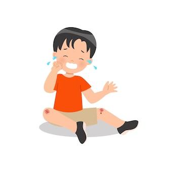 Trauriger junge, der über seinem blutenden knie weint