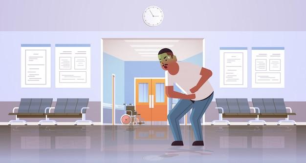 Trauriger kerl erbrechen übelkeit magenschmerzen essen oder alkoholvergiftung verdauungsproblem konzept afroamerikaner mann kotzen sich krank krank modernen krankenhaus korridor innenraum in voller länge horizontal