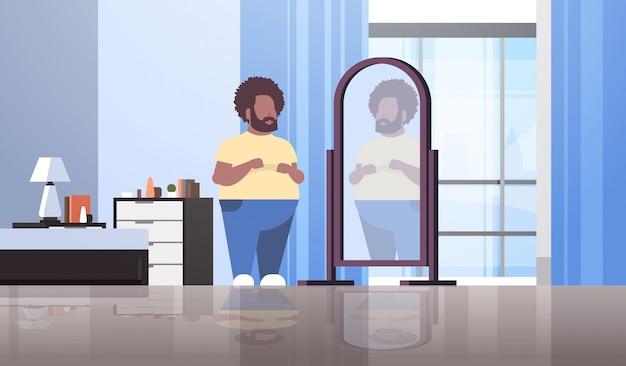 Trauriger mann, der spiegelbild im modernen apartmentschlafzimmer des spiegelmannskonzepts betrachtet